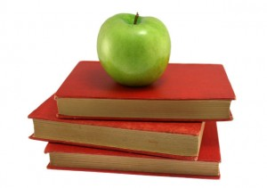 apple on stack of red books for back to school